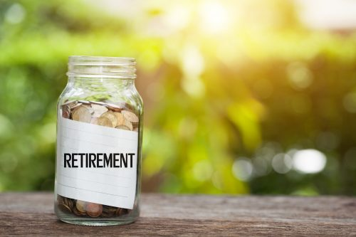 RETIREMENT word with coin in glass jar Savings and financial investment concept.